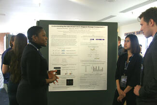 Students talking in front of a research poster