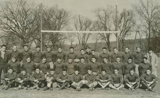Black-and-white photo of players posing on field.