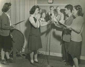 Black-and-white photo of students standing around a microphone.