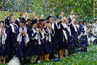 Graduates in caps and gowns celebrating with confetti.