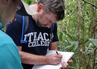 A man writing notes in the jungle