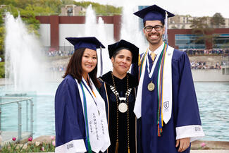 Shirley M. Collado with two students in caps and gowns in front of fountains