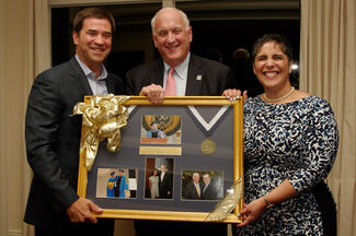 Two men and a woman pose as they hold a framed piece that showcases several photos and a medal.