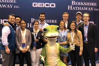 A group of people posing with the Geico gecko