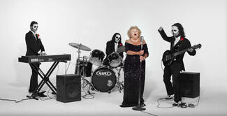 An older woman in black sings while men in black suits and skull makeup play instruments.