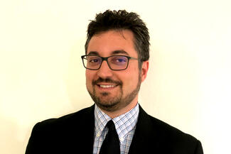A bearded man wearing glasses and a business suit
