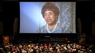 A photo of an older woman shone on an auditorium screen