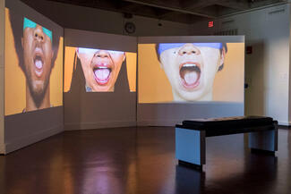 Three blindfolded faces with mouths wide open are projected on individual screens on gallery wall.
