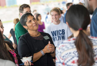 A woman listens intently as she speaks with a group of college students.