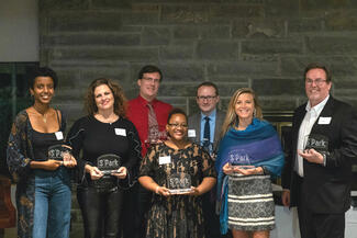 A group of men and women holding glass awards