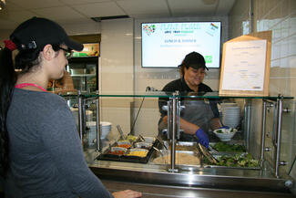 A woman at a counter puts food in a bowl