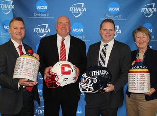Athletic directors and football coaches from SUNY Cortland and Ithaca College holding the Cortaca jugs and football helmets