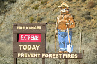 "A sign with ""Smokey the Bear"" warning about the extreme risk of forest fire"