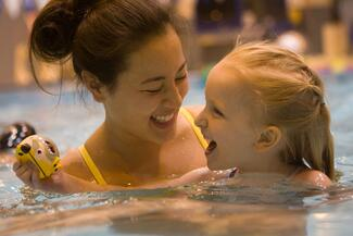 A student with a child in the pool
