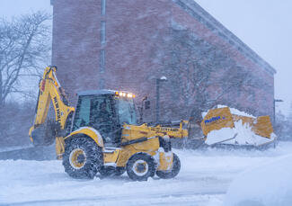 Front loader removing snow from parking lot