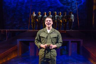 A man in military fatigues sings on stage