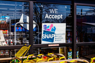 A storefront with a sign about SNAP