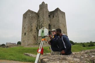 Two men use a 3D scanner outside of a castle