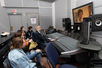 man in front of an audio mixing board teaches students