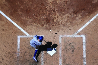 Baseball player hitting the ball from home plate from an aerial view