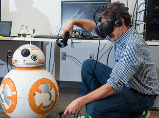 A man wearing VR goggles with a droid