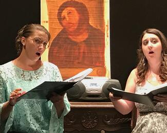 two women singing with a painting behind them