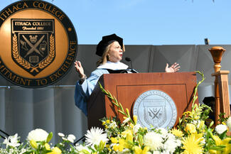 speaker with the Ithaca College seal behind her