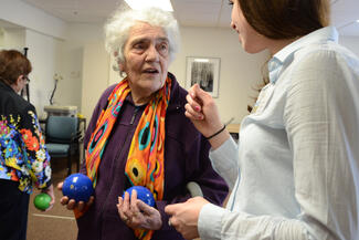 An elderly woman is holding two small blue balls standing up and speaking with a student in a white shirt