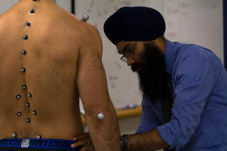 A man in a blue shirt is placing sensors on a man without a shirt on along various muscles so that he can measure his movements when he begins to run.