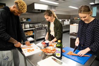 This is a picture of three students working in the food and nutrition lab. Each of them is standing at the kitchen island and they are chopping carrots.