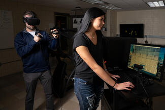 One student in dark clothes is standing in the background with a virtual reality headset on. Another student in a blue shirt is standing at a computer screen watching the study react to volleyball players.