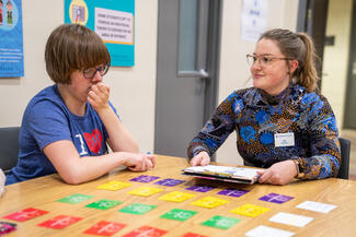 A student in a colorful shirt and glasses is sitting at a table with a young client. There are multi-colored cards spread out on the table in what looks like a game. The two are having a conversation