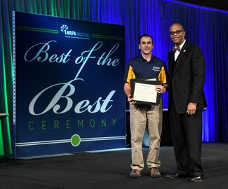"A person in a blue shirt and tan pants is holding an award plaque next to a man dressed in a suit. In the background is a poster that says ""Best of the Best"" Ceremony"