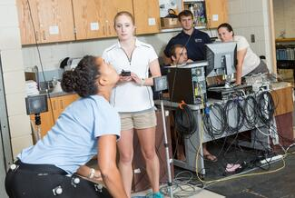 One student in a light blue shirt and black stretch pants has sensors attached to her legs and is about to jumping as high as they can. Another student in a white shirt and tan shorts is standing to the side with a sensor observing the student's movements.