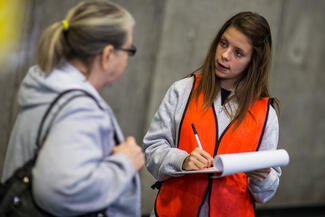 A student in an orange safety vest holding a clipboard is speaking to a person asking questions and writing them down on the clipboard.