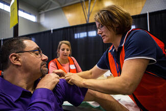 A person in a purple shirt is seated and pulling up the sleeve so that a person with a flu shot is able to administer the shot in the arm. A student stands in the background making notes.