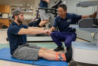 "A faculty member in a blue shirt is crouched down next to a student sitting in an ""L"" shape position pulling on a weight. A machine that is next to them is measuring the student's arm strength."