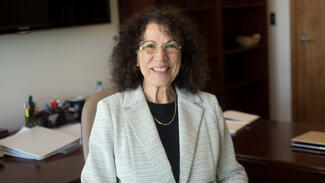 This is a photo of Linda Petrosino, Dean of the School of Health Sciences and Human Performance sitting at her desk.