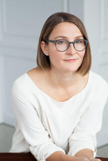 Eleanor Henderson in a white scooped-neck shirt and glasses.