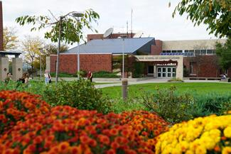 A college building with flowers in the foreground