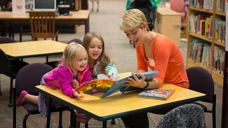 A young woman reading to two children