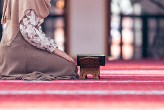 A woman kneeling in a mosque