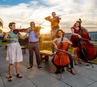 a group of five students plays string instruments outdoors on a patio