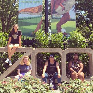 four women sit on a large concrete sculpture that says ZOO