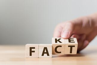 A hand moving lettered blocks spelling FACT to FAKE