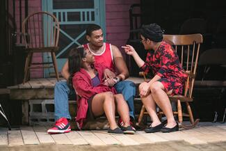 Scene from 'In the Red and Brown Water' depicting a young male and female couple speaking to an older female character.