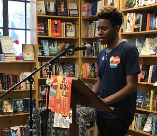 Student Jalen Lisbon reading at a podium in a bookstore.