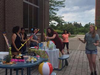 a group of students outside at a party with squirt guns and beach balls