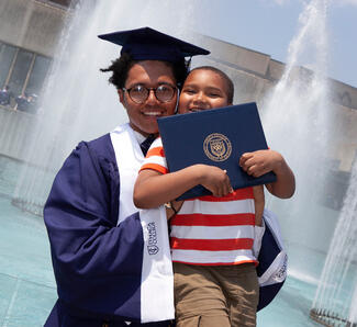 A graduating student poses with a younger child after the ceremony.
