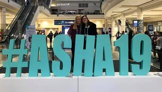 There are two students standing behind a large turquoise sign that reads #ASHA19
